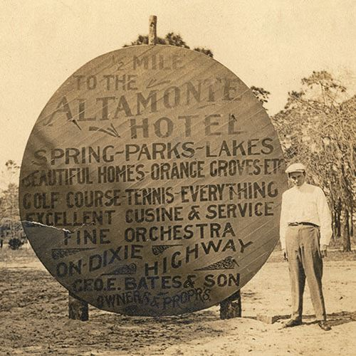 Man Standing By a Roadside Sign for the Altamonte Hotel